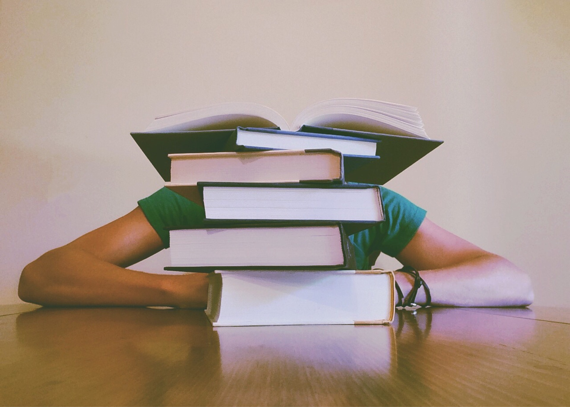 Student hiding behind a pile of books